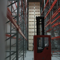 high stacking of wooden boxes for fruits in cold storage room